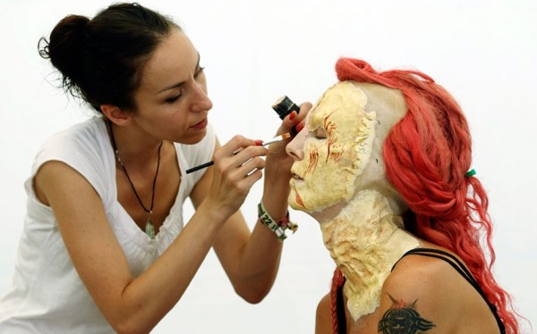A girl is painting on the body.