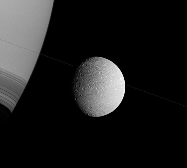 Saturn, Dione and subtle, seen nearly edge-on, the rings of the planet