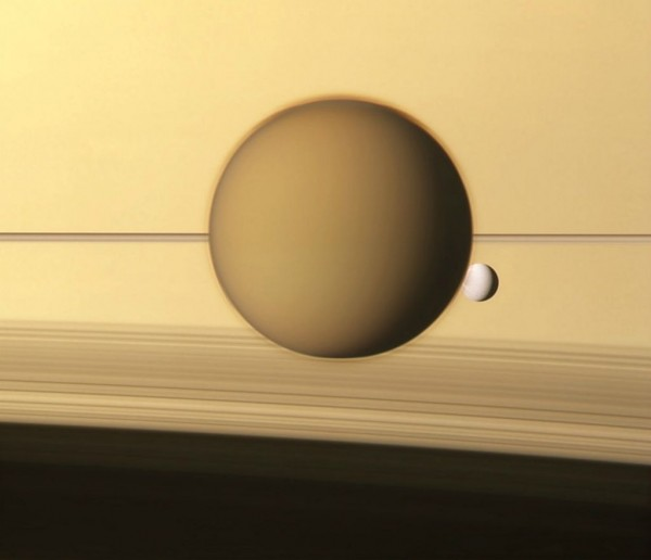 Titan and Dione against the outwardly serene atmosphere of Saturn