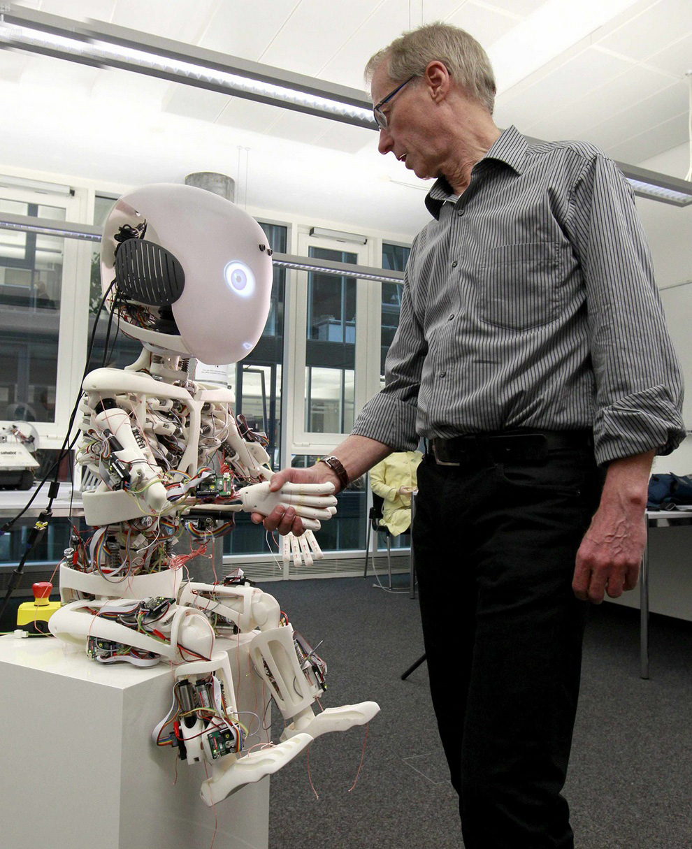 Director of the Laboratory of Artificial Intelligence Rolf Pfeifer shakes hands with his creation