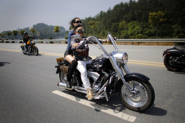 Young man and woman riding a motorcycle Harley Davidson during the annual rally at Lake Qiandaohu in Zhejiang Province, China.
