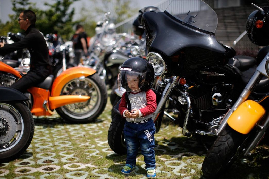 Local boy is photographed near the Harley Davidson motorcycle at the annual rally