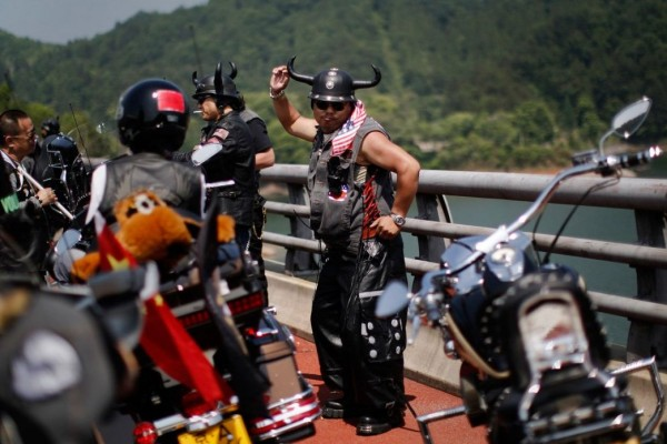 Biker dancing at the annual Harley Davidson rally at Lake Qiandaohu in Zhejiang Province, China