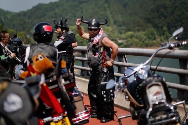 Biker dancing at the annual Harley Davidson rally at Lake Qiandaohu in Zhejiang Province, China