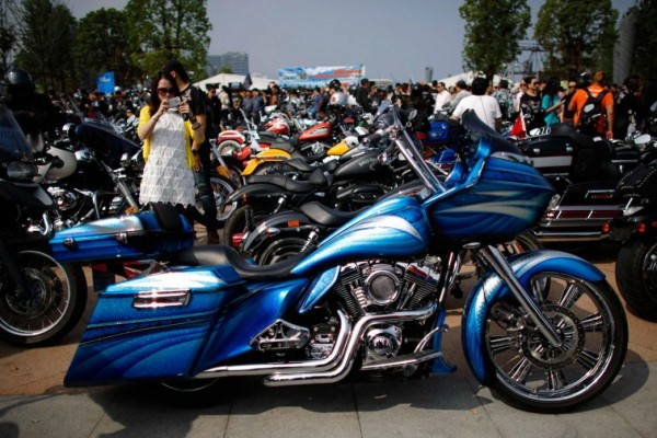 A woman photographs the Harley Davidson motorcycle during the annual rally