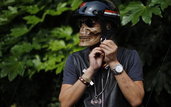 A man in a mask skeleton is preparing to participate in the annual Harley Davidson rally