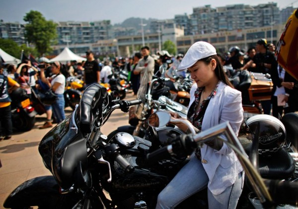 A woman sits on a Harley Davidson motorcycle during the annual rally at Lake Qiandaohu in Zhejiang Province, China.