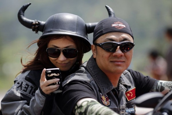 Young man and woman riding a motorcycle Harley Davidson during the annual rally in Qiandaohu Lake in Zhejiang Province, China
