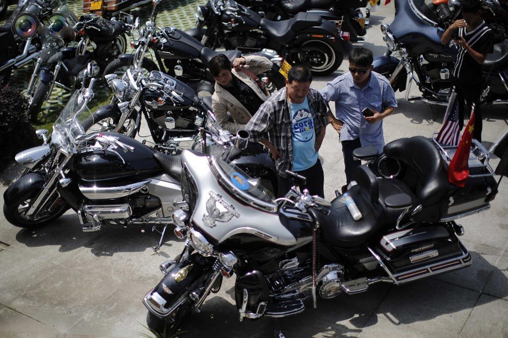 Local residents inspect a Harley Davidson motorcycle during the annual rally