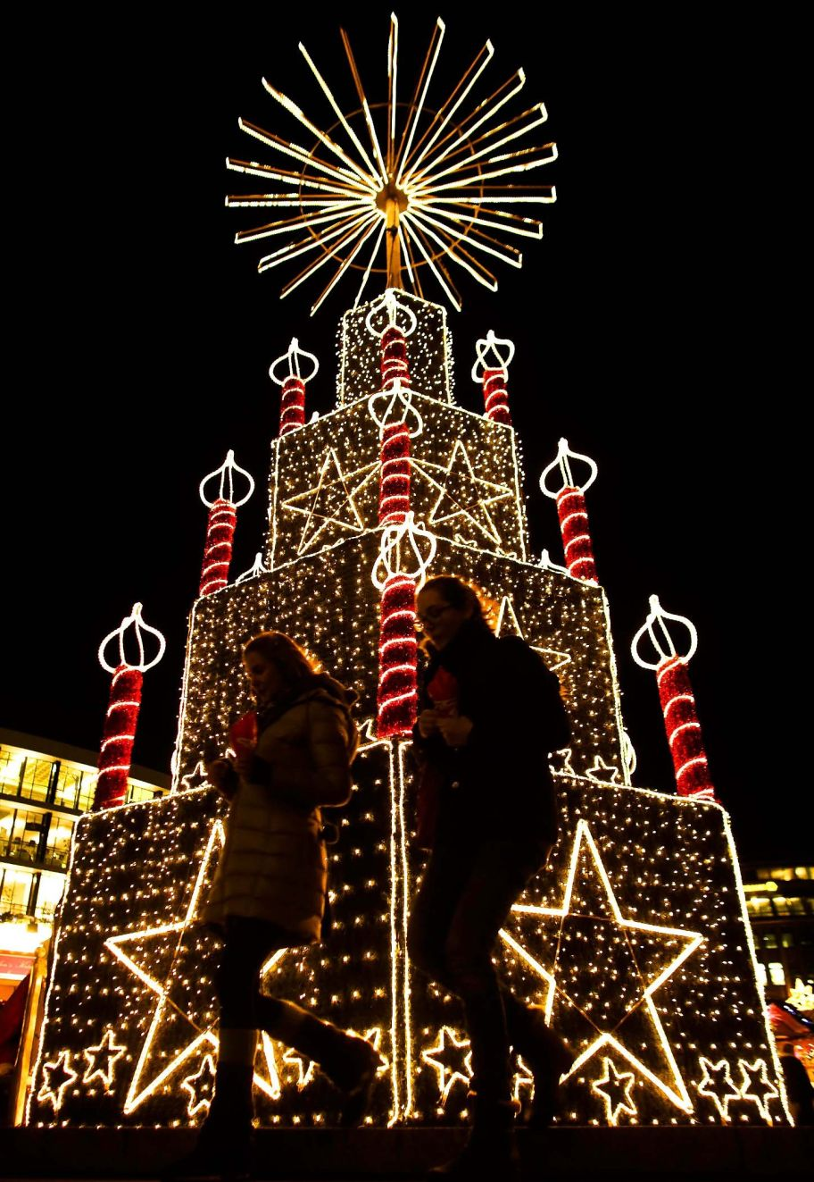 Two women on the background illumination of the Christmas fair in Berlin