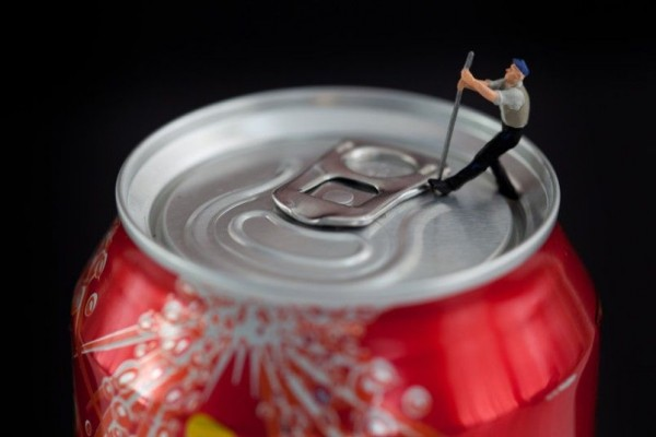 Tiny worker uses a crowbar to open a jar of Coca-Cola