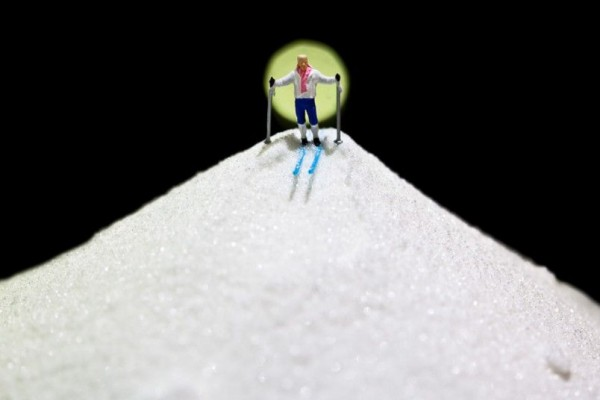 While a miniature skier prepares to make his way down a mountain of granulated sugar