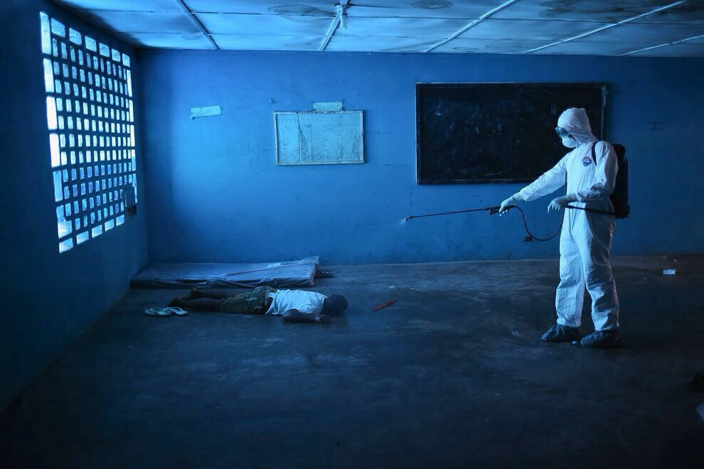 A health worker disinfects a corpse in an Ebola isolation ward, once a primary school, in Mornovia, Liberia