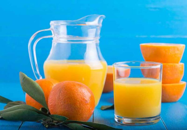 fresh tangerines, oranges, orange juice on a blue background