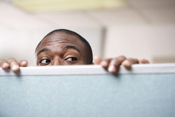 Businessman peeking over cubicle wall